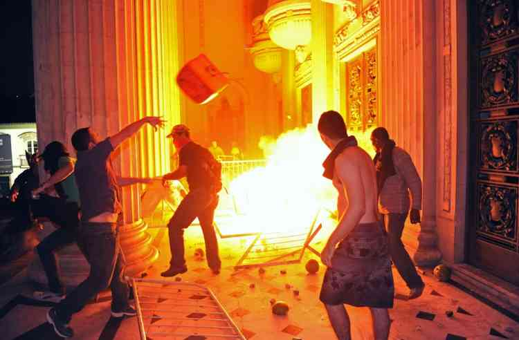 Demonstrators set fire outside the Tiradentes Palace -- Rio de Janeiro's Legislative Assembly (ALERJ)-- during a protest in Rio de Janeiro, on June 17, 2013. Tens of thousands of people took to the streets of major Brazilian cities protesting the billions of dollars spent on the Confederations Cup --and preparations for the upcoming World Cup-- and against the hike in mass transit fares.   AFP PHOTO / TASSO MARCELO