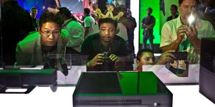 Des visiteurs du salon E3 2013 à Los Angeles observent la nouvelle Xbox One de Microsoft.