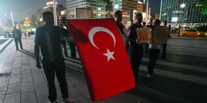 Des manifestants turcs brandissent un drapeau de leur pays, à Ankara, le 20 juin.