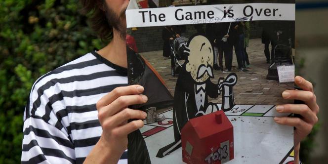 Un manifestant brandit une pancarte fustigeant le renflouement jugé trop généreux des banques britanniques victimes de la crise, le 19 juin à Londres.
