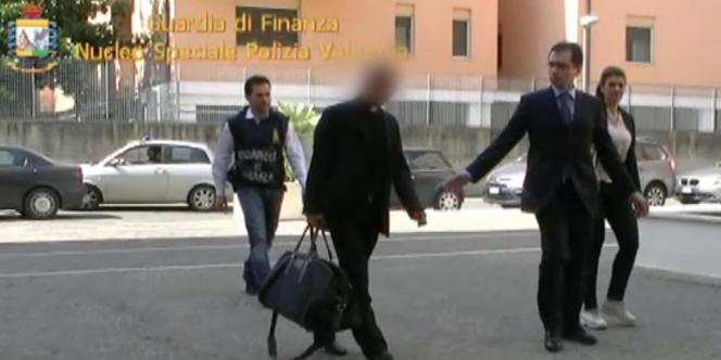 Membre de l'administration du patrimoine du siège apostolique, qui gère les biens du Vatican, Nunzio Scarano est escorté par le police après son arrestation, le 28 juin à Rome.