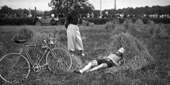Sous le regard d'un spectateur, le cycliste français Amédée Fournier se repose dans un champ lors d'une étape du Tour de France en juillet 1939 à Pau.