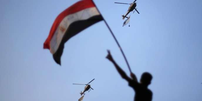 Des hélicoptères de l'armée égyptienne déploient le drapeau national sous les applaudissements de la foule réunie place Tahrir, le 1er juillet au Caire.