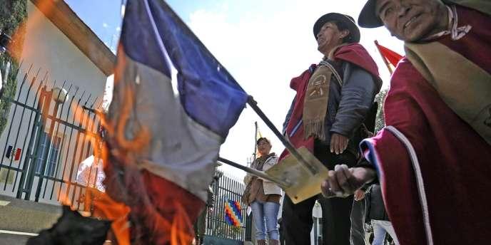 Des manifestants brûlent un drapeau tricolore devant l'ambassade de France à La Paz.