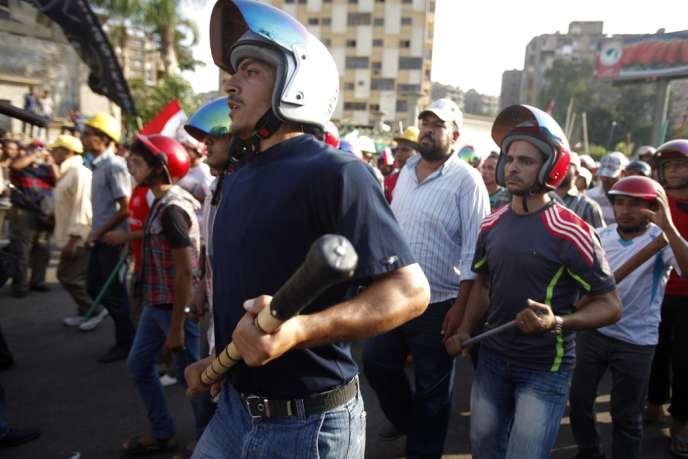 Casqués et armés de manches de pioches ou de barres de fer, des partisans du président égyptien islamiste Mohamed Morsi, défilent dans les rues du Caire.