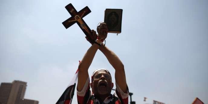 Un opposant à Morsi brandit une copie du Coran et une croix chrétienne durant un rassemblement place Tahrir, vendredi 5 juillet.