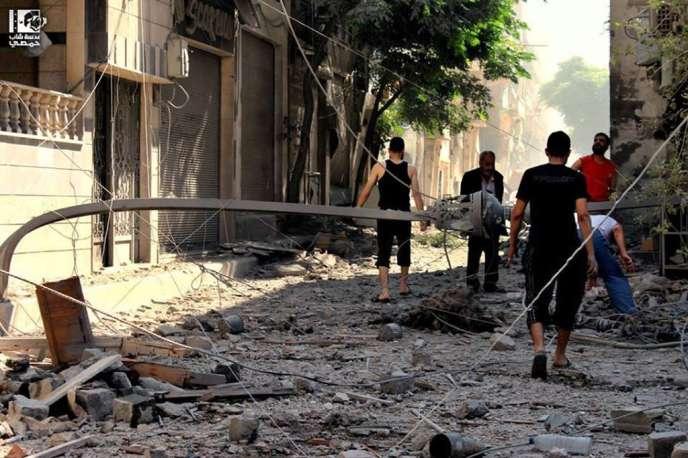 Des habitants d'Homs inspectent les dommages causés par un bombardement de l'armée.