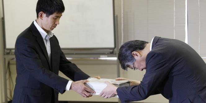 Tomoya Ichimura (à gauche), un des responsables de l'ARN, reçoit d'Osamu Sakai, vice-président d'Hokkaido Electric Power Company, les doléances de l'entreprise, lundi 8 juillet, à Tokyo.