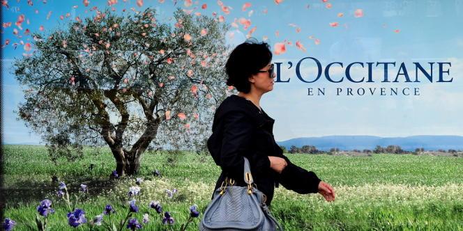 Une femme passe devant une publicité pour L'Occitane à Hongkong.