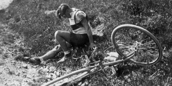 Un coureur cycliste du Tour de France se tient sur le bord de la route après avoir chuté lors d'une étape de la Grande Boucle, en juillet 1933.
