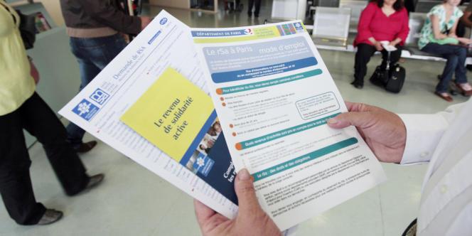 Une personne présente les brochures informant sur le revenu de solidarité active (RSA) mises à la disposition des usagers dans un centre de la caisse d'allocations familiales (CAF) à Paris.
