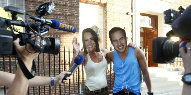Des équipes de télévision portant des masques du prince William et de Kate devant l'entrée de la Lindo Wing, la maternité privée de l'hôpital St. Mary, à Londres, le 18 juillet.