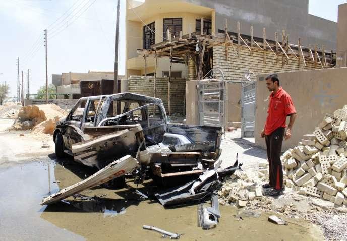Un homme inspecte sa voiture détruite par un attentat, à Bagdad, le 24 juillet.