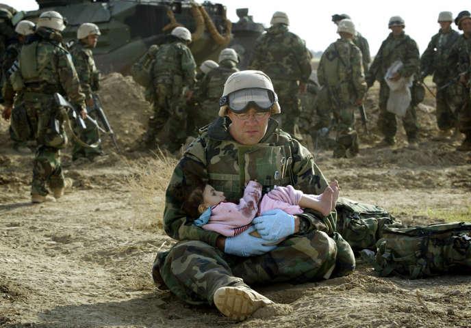 Le 29 mars 2003, un marine tient une petite fille irakienne dans ses bras après que son unité a tiré sur un véhicule de civils, tuant la famille de l'enfant. Ce véhicule était poursuivi par des tireurs irakiens, ce qui le forçait à se diriger vers la base américaine.