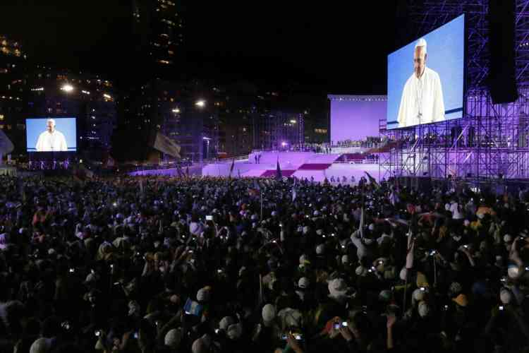 "Pope Francis, seen on a giant screen, speaks to pilgrims gathered on the Copacabana beachfront in Rio de Janeiro, Brazil, Thursday, July 25, 2013. Francis addressed young pilgrims from 175 nations gathered on the famous beach, as he continued his inaugural international trip as pontiff. Francis showed his rebel side Thursday, urging young Catholics to shake up the church and make a ""mess"" in their dioceses by going out into the streets to spread the faith. (AP Photo/Jorge Saenz)"