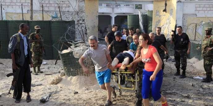 Des personnels de l'ambassade turque en Somalie évacuent leurs collègues blessés, samedi, après un attentat-suicide.