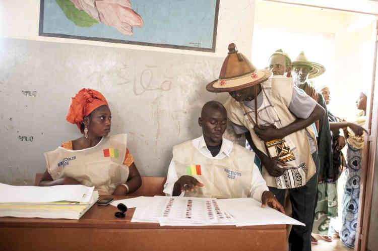28/07/2013. Konna. Mali. Jour des Žlections prŽsidentielles maliennes. Deux assesseurs contr™lent le carte d'Žlecteur d'un votant. ©Sylvain Cherkaoui pour Le Monde