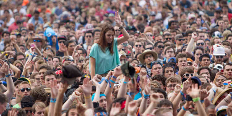 Fans watch Canadian electronic band Crystal Castles perform at Lollapalooza Festival in Chicago, Friday, Aug. 2, 2013. The more than two-decade-old festival opens Friday in Chicago's lakefront Grant Park. (AP Photo/Scott Eisen)