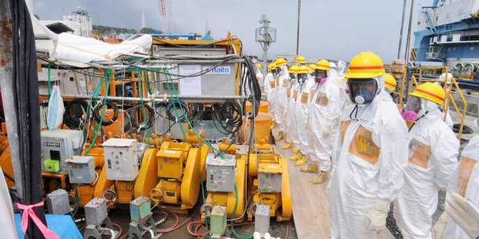 Des travailleurs de Fukushima, chargés de contrôler le démantèlement de la centrale, inspectent la construction de barrières censées empêcher l'écoulement d'eau contaminée dans l'océan.