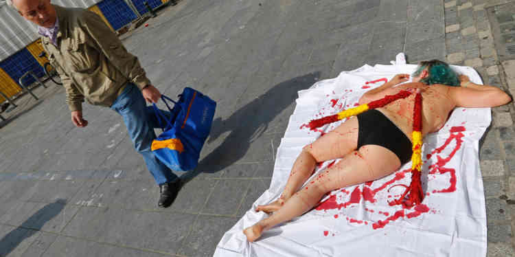 An animal rights protester covered in fake blood, lies on the pavement during a demonstration calling for the abolition of bullfights, in central Brussels August 8, 2013.       REUTERS/Yves Herman (BELGIUM - Tags: ANIMALS CIVIL UNREST)
