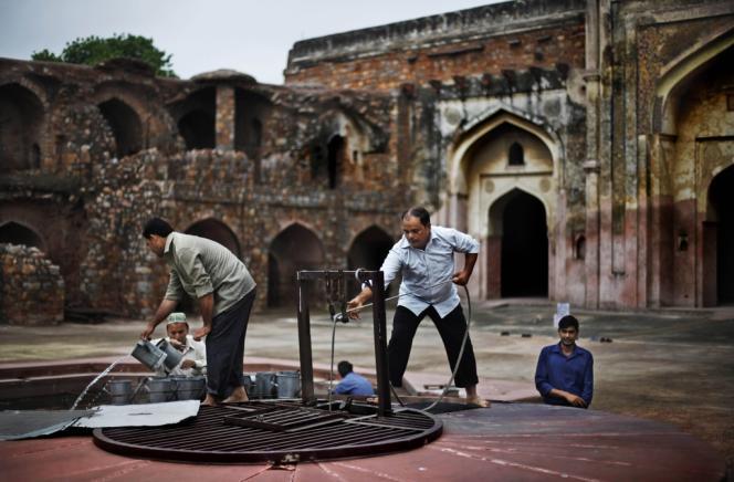 Des Indiens puisent de l'eau  près d'une mosquée de la capitale, New Delhi, le 12 juillet.
