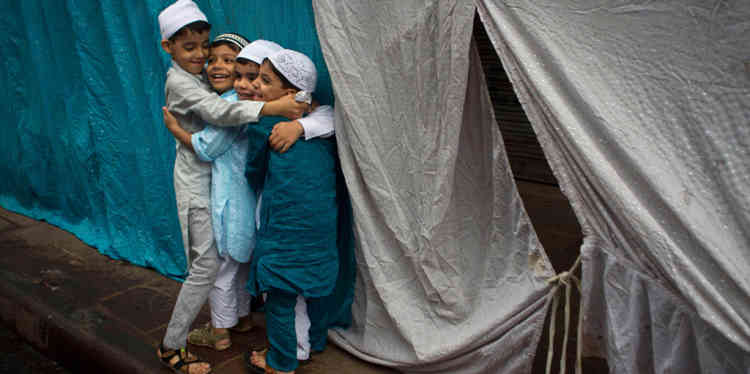 Indian Muslim children hug and wish each other after offering Eid prayers in New Delhi, India, Friday, Aug. 9, 2013. Eid al-Fitr marks the end of the holy month of Ramadan, during which Muslims all over the world fast from sunrise to sunset. (AP Photo/Tsering Topgyal)