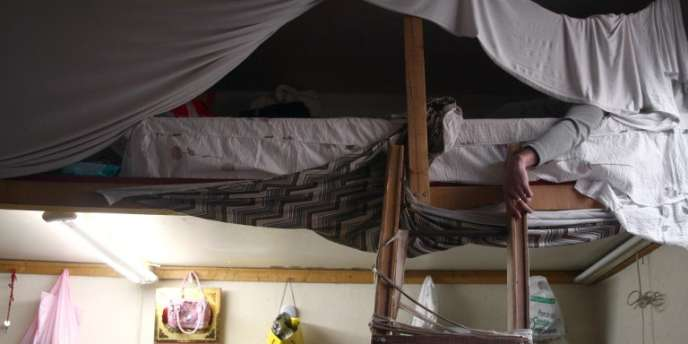Un sans-papiers chinois est allongé dans son lit, le 22 octobre 2007 dans son appartement à Paris.