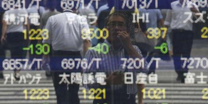 Devant un écran affichant les cours de la bourse de Tokyo, le 12 août.