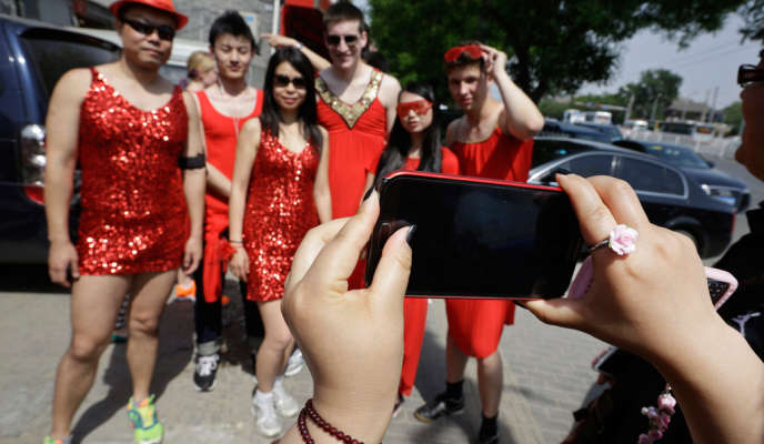 A woman uses her Samsung mobile phone to take a picture before a Red Dress run event in Beijing in this May 12, 2013 file photo. Samsung, the South Korean giant, now has a 19 percent share of the $80 billion smartphone market in China, a market expected to surge to $117 billion by 2017, according to International Data Corp (IDC). That's 10 percentage points ahead of Apple, which has fallen to 5th in terms of China market share. Picture taken May 12, 2013. To match Insight story SAMSUNG-APPLE/CHINA REUTERS/Jason Lee/Files (CHINA - Tags: BUSINESS TELECOMS)