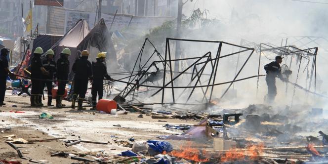Des pompiers tentent d'éteindre un feu alors que les forces de sécurité évacuent un