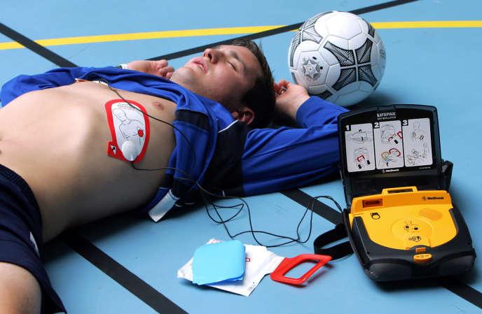 Une personne pose des électrodes d'un défibrillateur externe automatique (DEA) sur un jeune homme, le 19 Mai 2006 dans une salle de sport de la Chapelle d'Armentières, lors d'une présentation de l'appareil délivrant un choc électrique à une personne en souffrance cardiaque.