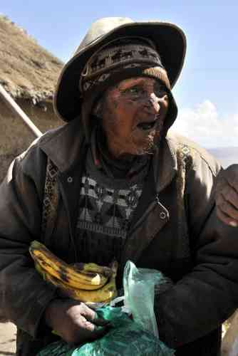 Bolivian Carmelo Flores Laura, an Aymara native who claims is 123 years old and if confirmed would be the oldest man alive, holds some bananas and a bag full of coca leaves outside his house in the community of Frasquia, 4050 metres above sea level, on the foothills of the Illampu snowcapped mountain in the Bolivian Andes, some 150 km east of La Paz, on August 15, 2013. The Bolivian Government will check documents that say Flores was born on July 16, 1890 to verify if he indeed is the oldest living person.   AFP PHOTO / Aizar RALDES