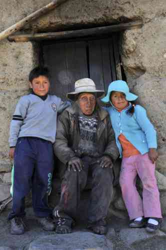 Bolivian Carmelo Flores Laura, an Aymara native who claims is 123 years old and if confirmed would be the oldest man alive, is accompanied by great-granchildren Edgar (L) and Gloria, outside his house in the community of Frasquia, 4050 metres above sea level, on the foothills of the Illampu snowcapped mountain in the Bolivian Andes, some 150 km east of La Paz, on August 15, 2013. The Bolivian Government will check documents that say Flores was born on July 16, 1890 to verify if he indeed is the oldest living person.   AFP PHOTO / Aizar RALDES