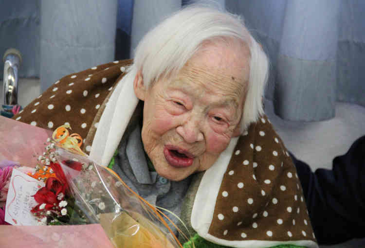 This handout picture taken by Tomohito Okada from the Kurenai nursing home on March 5, 2013 shows the world's oldest woman Misao Okawa celebrating her 115th birthday after receiving flowers at the nursing home in Osaka, western Japan. Okawa, who late last month received a certificate from Guinness World Records confirming her status as the oldest living woman, celebrated her 115th birthday on March 5 in a Japanese nursing home with her favourite mackerel sushi dish on the menu.         AFP PHOTO / TOMOHITO OKADA / MURSING HOME KURENAI