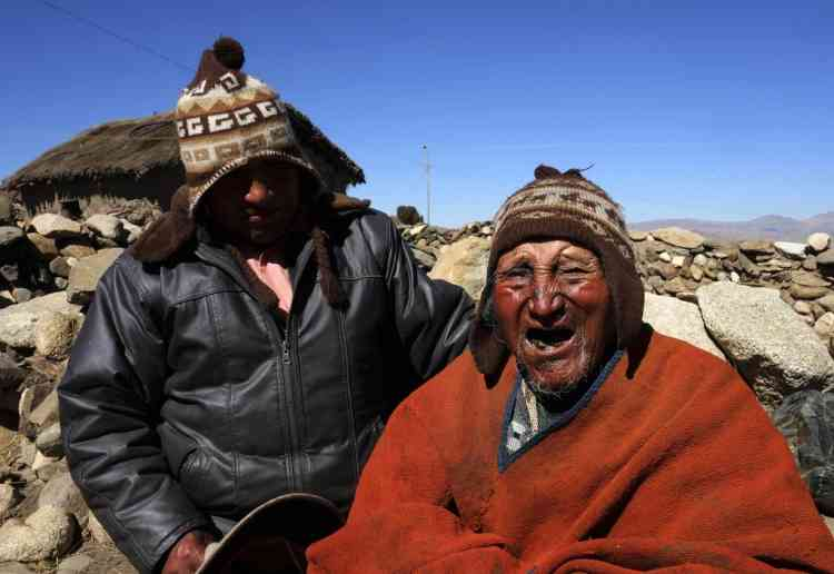 Aymara Indian Carmelo Flores (R) and his son Cecilio joke during a Reuters TV interview in his hometown of Frasquia, 110km (68 miles) north of La Paz, August 16, 2013. According to Flores' identification card, he was born in 1890 and celebrated his 123rd birthday last month, making him the world's oldest man. Flores, who used to work as a farmer, has lived next to Bolivia's highest mountain, the Illampu, for his entire life. He eats what can hunt, like snake, lizard and fox, only drinks mountain spring water, chews coca leaves, avoids sugar and says that he has never been seriously ill.      REUTERS/David Mercado  (BOLIVIA - Tags: SOCIETY)