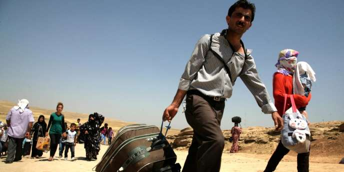 Des réfugiés syriens traversant la frontière du Kurdistan irakien enaoût2013.