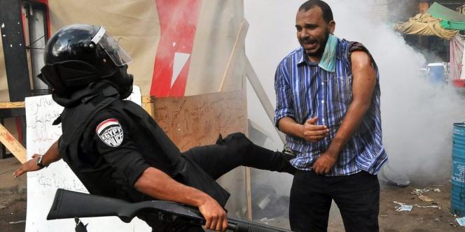 Un policier frappe un partisan de Mohamed Morsi lors de l'évacuation d'un sit-in au Caire le 14 août.