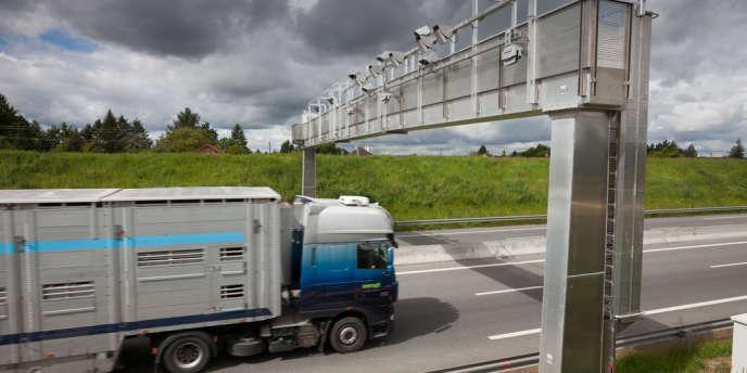 Poids lourd passant sous un portique de contrôle de présence du GPS pour le paiement de l'écotaxe.