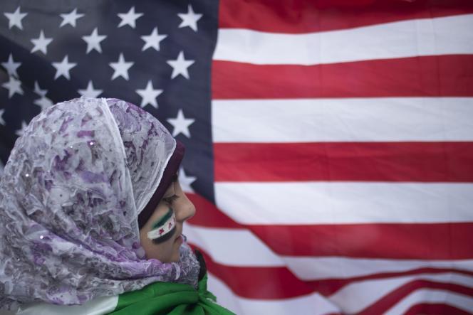 Une jeune réfugiée syrienne devant un drapeau américain, lors d'une manifestation devant le siège des Nations unies, le 21 août à New York.