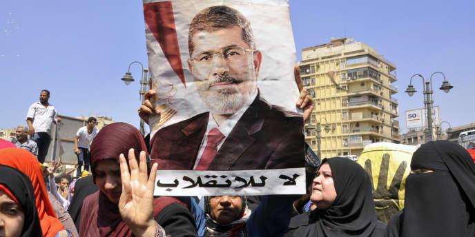 Des partisans des Frères musulmans manifestent au Caire le 30 août et brandissent le portrait de Mohamed Morsi.