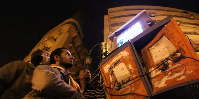 Des égyptiens regardent Al-Jazira place Tahrir, au Caire, en juin 2011.