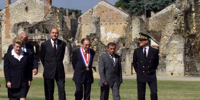 Jacques Chirac (3e G), accompagné de la ministre Catherine Trautmann (G), traverse, le 16 juillet 1999, ce village martyr avant de participer à l'inauguration du Centre de la Mémoire.