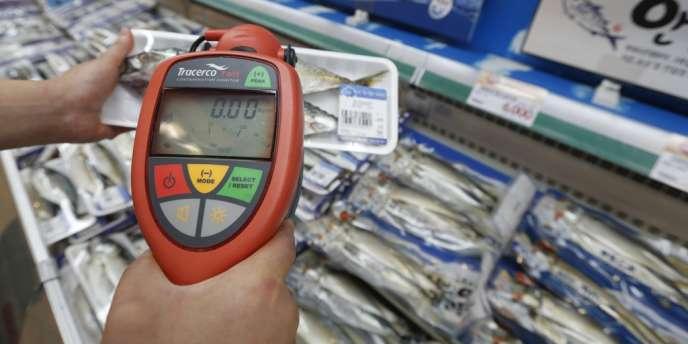 Un employé d'une grande surface de Séoul passe un compteur Geiger sur des produits de la mer pour montrer qu'ils ne sont pas radioactifs.