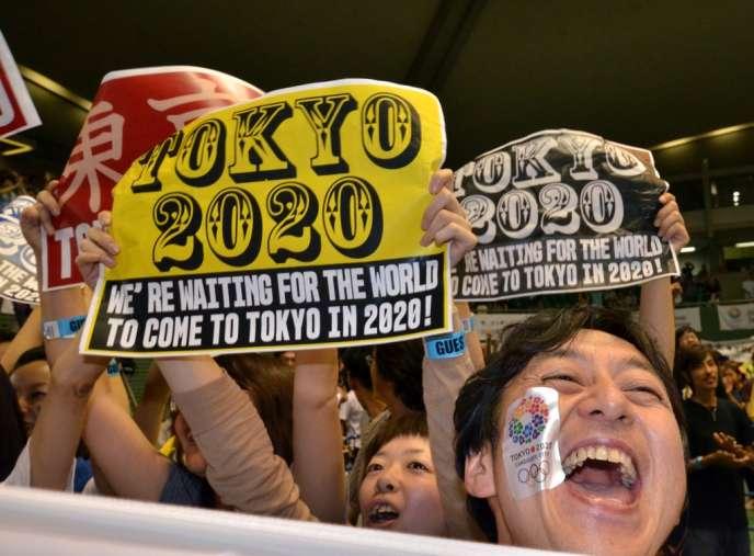 Des Japonais célèbrent, à Tokyo, la victoire de leur ville, qui a gagné le droit d'organiser les JO en 2020, le 7 septembre.