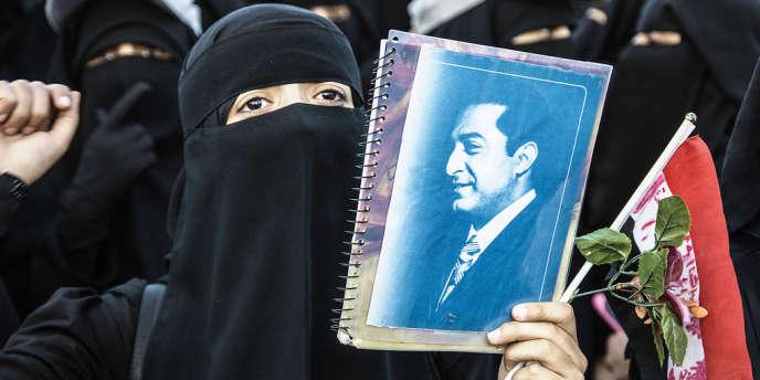 En 2012, lors d'une manifestation à Sanaa contre la corruption, une femme brandit le portrait de l'ancien président.