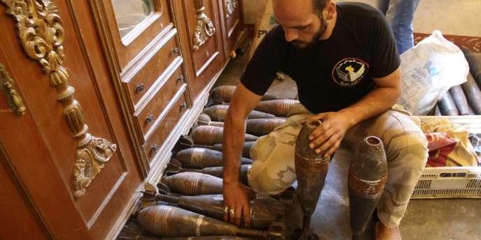 Un membre de l'armée syrienne libre devant des obus de mortiers, à Alep, le 10 septembre.