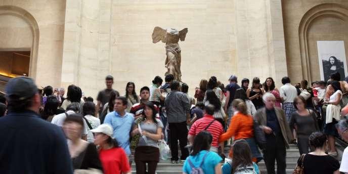Des visiteurs devant la Victoire de Samothrace, au Louvre, le 17 juin 2009.