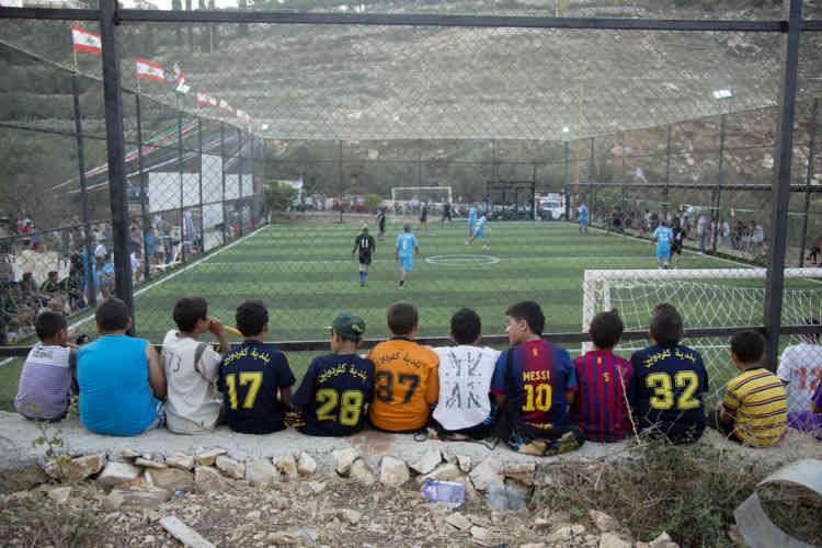 Des enfants regardent un match de football entre des footballeurs du village et des soldats du contingent Francais de la FINUL et d'autres du contingent Indonisien dans le village de Kfar Danoune, au sud du Liban, pendant l'inauguration d'un terrain de football, le Vendredi 13 Septembre, 2013.
