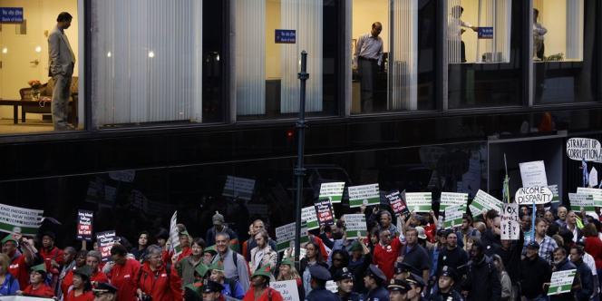 Des employés de la Bank of India regardent passer la manifestation du mouvement Occupy Wall Street, le 17 septembre à New York.
