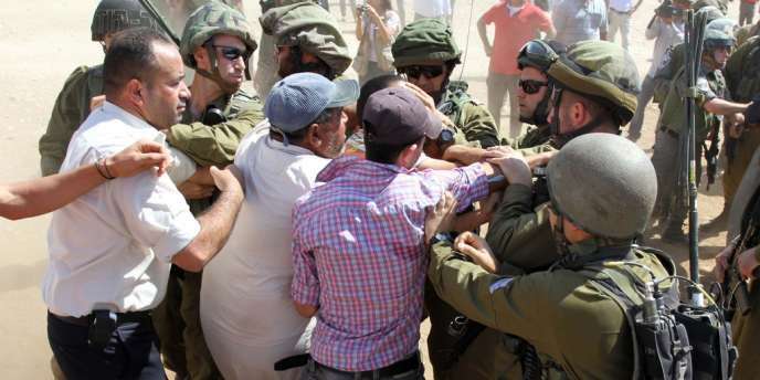 Des soldats israéliens contiennent des Palestiniens aux abords d'un camion de vivres, vendredi, en Cisjordanie.